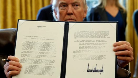 President Donald Trump holds up a signed executive order to advance construction of the Dakota Access
