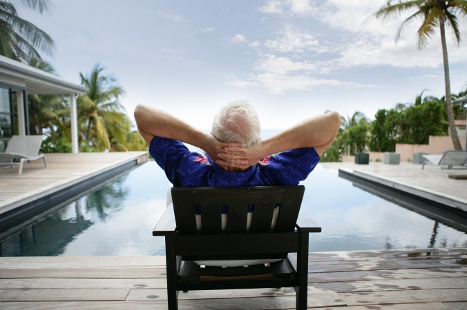 Older man relaxing by a luxurious pool